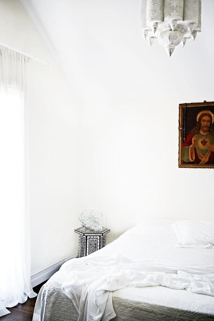 The master bedroom is rich with history, thanks to the Sacred Heart of Jesus artwork and an heirloom quilt Stylist: Glen Proebstel, Photographer: Mark Roper