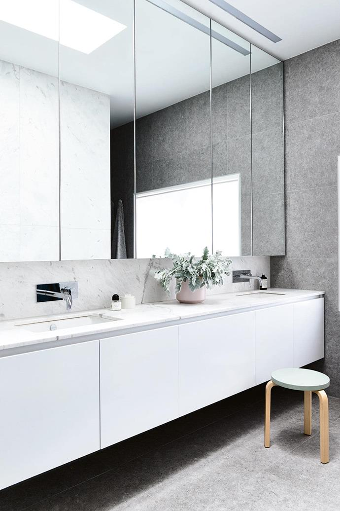 "Despite its [monochromatic colour scheme](https://www.homestolove.com.au/monochrome-bathrooms-6390|target=""_blank""), this bathroom manages to feel inviting and warm with an interesting combination of cement-look tiles, marble and timber."