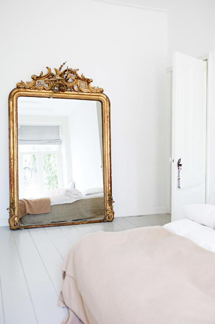 9. Upon reflection. A pared-back look takes centrestage in the master bedroom. A blank white canvas allows the textures of linen sheets and a wool blanket to bring a cosy feel. The bed's low height, as well as the large ornate mirror, allows the light coming in to enhance the ceiling height. Tip: A formal piece takes on a more relaxed air when propped securely against a wall Stylist: Jessica Bouvy, Photographer: Dana Van Leeuwen