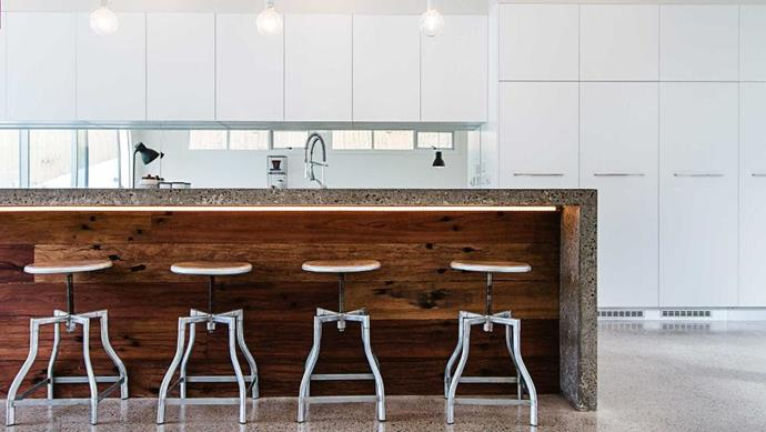 In this kitchen by [FutureFlip](http://futureflip.com.au) the concrete and timber bench and industrial style stools are off set by the clean lines of the white cabinetry. Architects: [Couvaras](http://couvaras.com) Photographer: Kieran Moore
