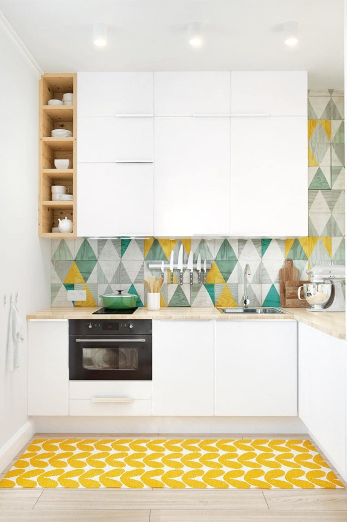 """**Geometric** Patterned tiles again come to the fore in this compact kitchen space. The splashback incorporates bright yellow and muted greens to add a pop of playfulness to the white ad timber space which is coupled with acolourful rug on the floor. *Design: [Spacecraft Joinery](http://spacecraftjoinery.com.au/ target=""""_blank"""" rel=""""nofollow"""")   Stylist: Emily O'Brien   Photographer: Jonathan VDK*."""