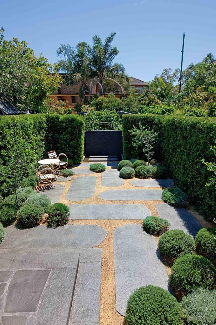Custom-cut pavers are laid in a broken pattern, drawing the eye around the garden, rather than imposing a single direction.
