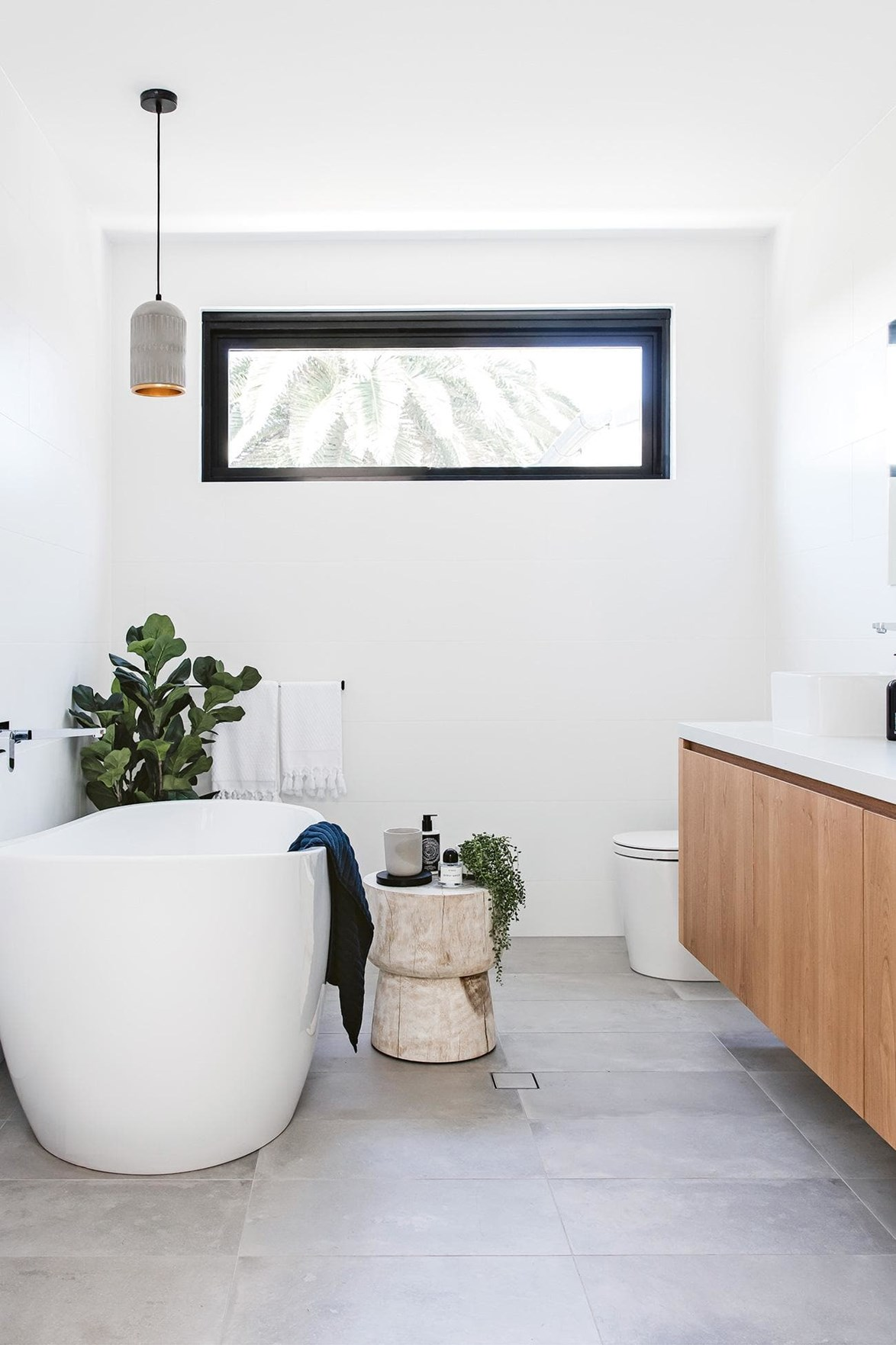 "A black steel-framed window punctuates a fresh white bathroom in a [modern home on the Northern Beaches](https://www.homestolove.com.au/step-inside-this-modern-northern-beaches-home-18400|target=""_blank""). *Photo: Maree Homer / Styling: Kristin Rawson*"