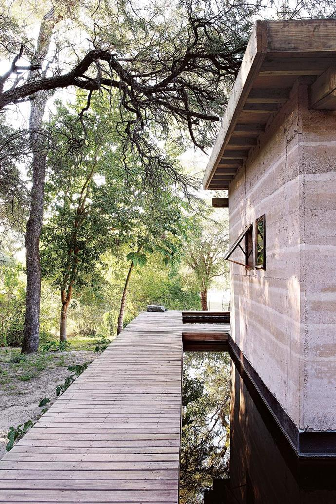 """**Exterior** A wooden walkway connects the main house to a guest cottage. [Read the full story here](https://www.homestolove.com.au/building-a-sustainable-rammed-earth-home-in-botswana-15548