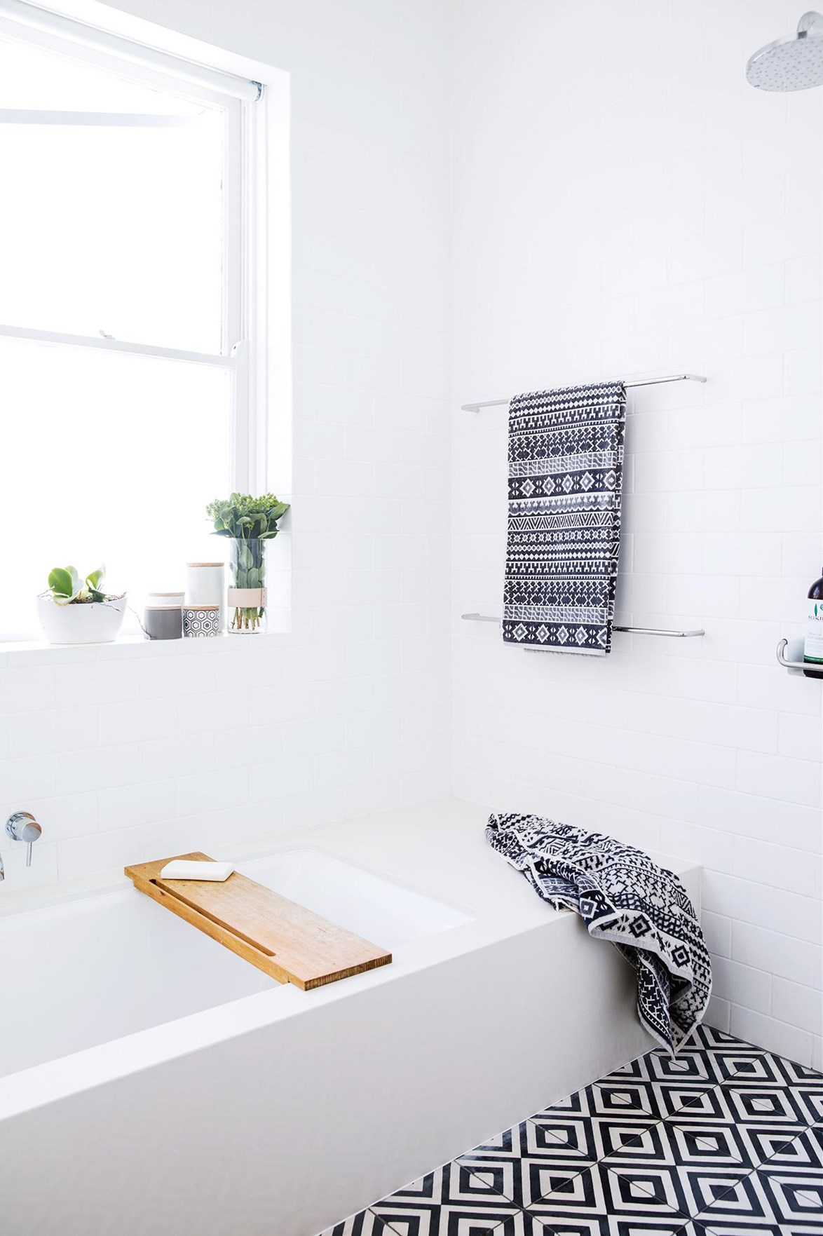 "This minimalist white bathroom in a [light filled terrace house](https://www.homestolove.com.au/minimalist-inspiration-from-a-light-filled-terrace-18366|target=""_blank"") is anything but dull with black and white patterned floor tiles."