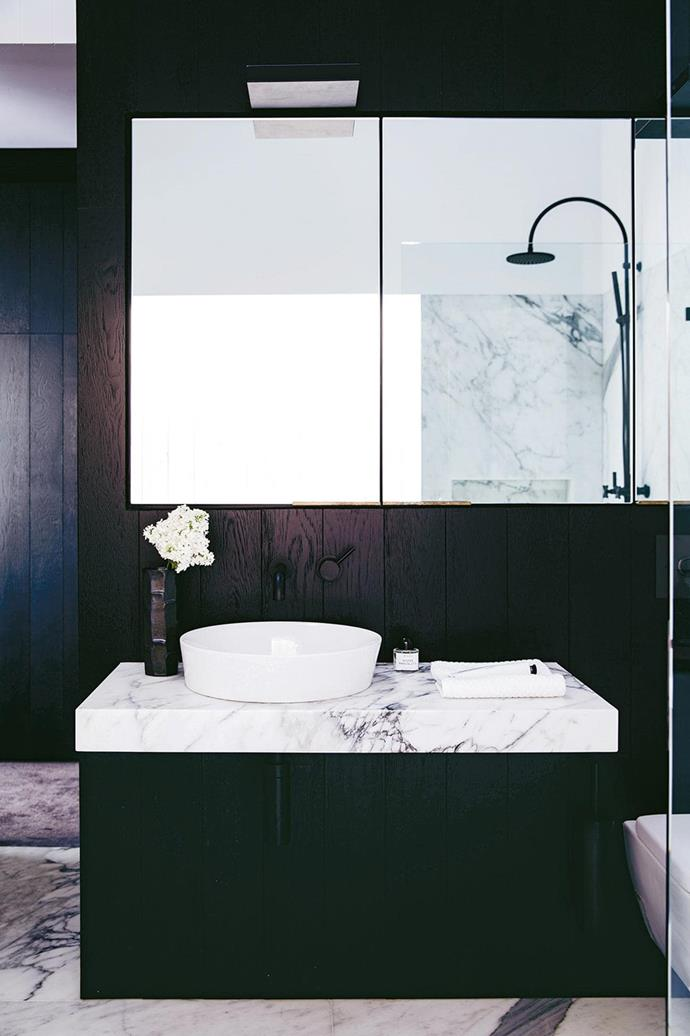 "Black joinery allows a floating calacatta marble vanity to take centre stage in this [luxurious ensuite bathroom](https://www.homestolove.com.au/ensuite-bathroom-design-ideas-18820|target=""_blank""). *Photo: Chris Warnes / Stylist: Stephanie Powell*"