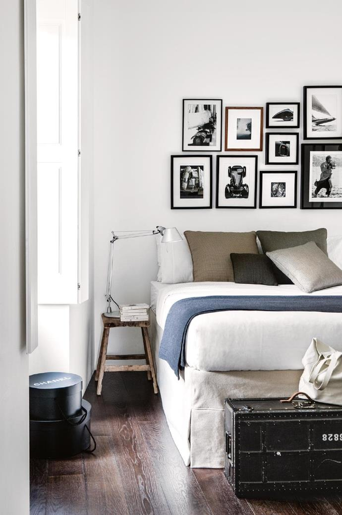 Fresh white linen is accented by subdued blues and browns. This bedroom features a curated display of artworks. Photographer: Stefania Giorgi