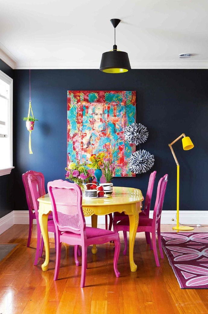 Dark inky walls are the perfect foil for this glossy yellow dining table and raspberry pink chairs Stylist: LeeAnn Yare, Photographer: Larnie Nicolson
