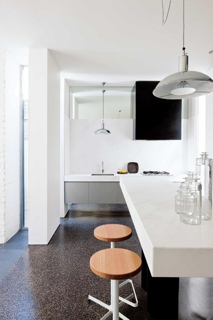The kitchen bench overlaps with the living room, doubling as a bar for guests. The sink and cooking areas are unified with a seamless Elba benchtop and splashback.