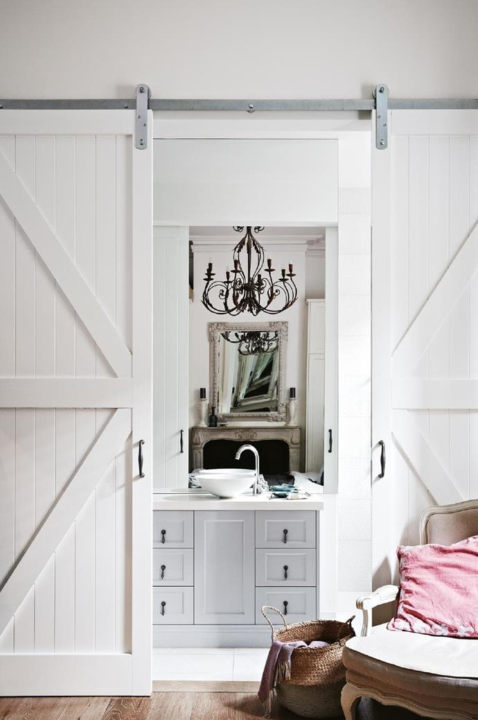 <strong>Lady luxe</strong>. So romantic, so pretty, so petite – but you wouldn't know it, right? That's down to two things: the barn doors, which are a great space-saving solution for a narrow footprint, and the oversized vanity-to-ceiling mirror. Reflecting that provincial-style chandelier and grand mantel makes them feel like part of the space. Clever as Stylist: Heather Nette King, Photographer: Armelle Habib