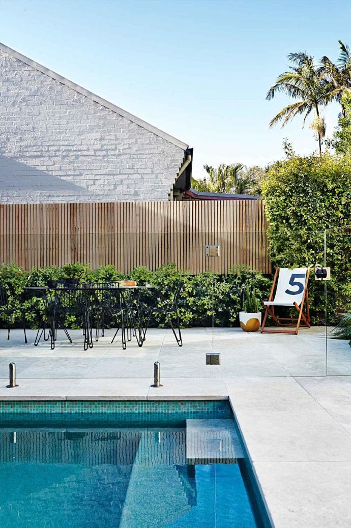 A New Zealand Christmas bush hedge and vertical paling fence provide a simple backdrop to the garden's entertaining area Photographer: Natalie Hunfalvay, Stylist: Adam Robinson