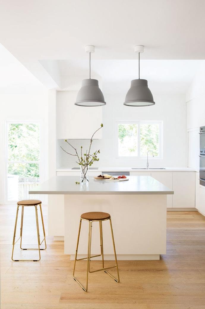 Muuto pendant lights illuminate this entertainer's zone, their tone complementing the Corian benchtop with stools from Great Dane adding a glint of brass