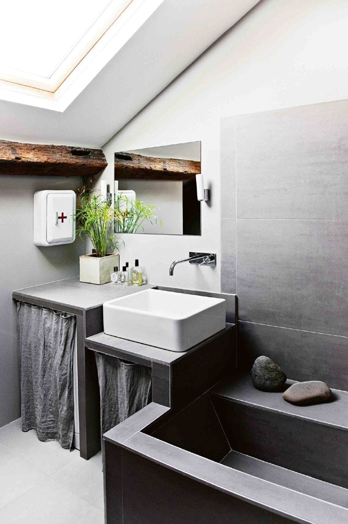 "A modular stone bench morphs into a bath tub which makes the most of the limited space. When renovating their [small Parisian apartment](https://www.homestolove.com.au/small-space-ideas-from-a-parisian-apartment-17037|target=""_blank""), the owner opted for deep grey hues to create a 'nest like' feel. *Photo: Morten Holtum / Living Inside / Styling: Lykke Foged / Story: Inside Out*"