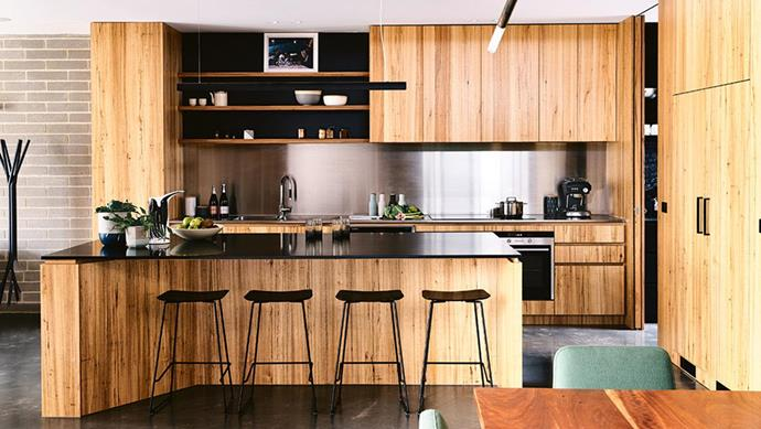 "In the kitchen of this [concrete brick and timber home](https://www.homestolove.com.au/concrete-brick-and-timber-ideas-from-a-contemporary-home-17933|target=""_blank""), a stainless-steel splashback contrasts with the warm messmate cabinetry. *Photo: Derek Swalwell*"