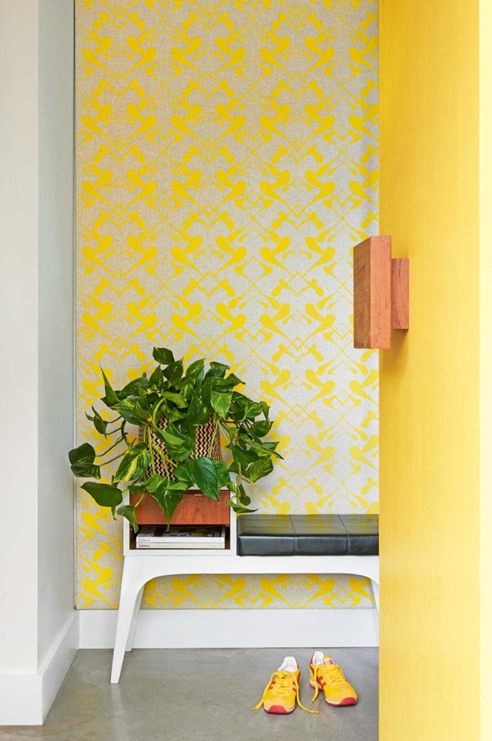 """A bright yellow door - complete with chunky wooden handle and [yellow patterned wallpaper](http://www.homestolove.com.au/whimsical-wallpaper-6635