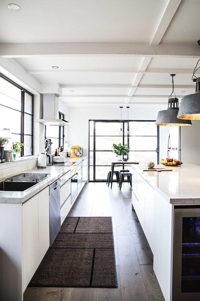 Natural light floods this kitchen, with white counters helping to amplify it. A large island bench ensures that there's plenty of room for prep and industrial-style pendant lamps are a stylish finishing touch Photographer: Sneh Roy