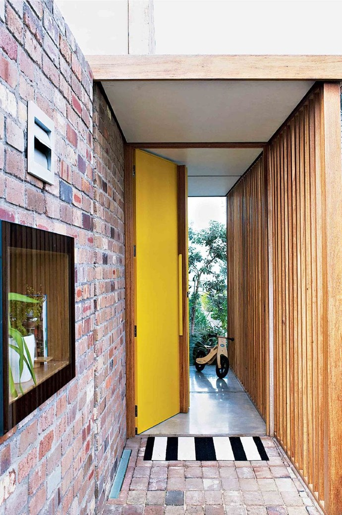 """Design elements from the exposed brickwork and timber panelling to the concrete floors and [extra wide yellow door](http://www.homestolove.com.au/statement-doors-are-the-latest-home-design-trend-5404