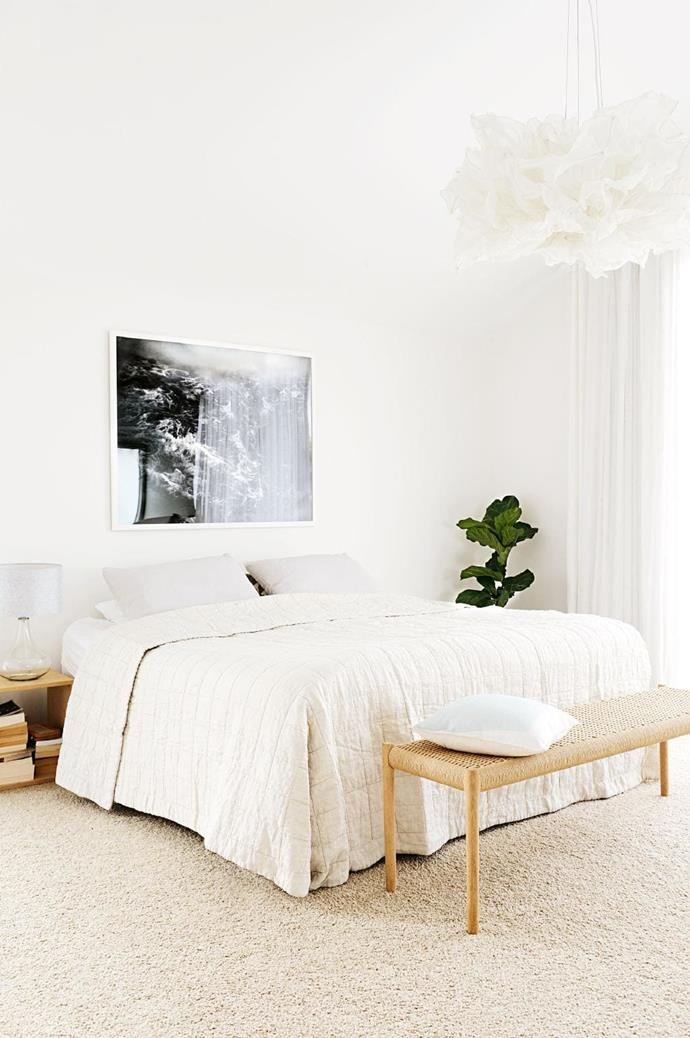 The neutral-toned palette of the bedroom echoes this home's light and airy feel, with the rattan benchseat at the foot of the bed adding a bright contrast. The statement pendant light adds a dreamy feel to the space.