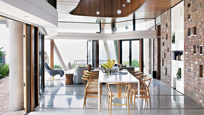 Mirroring the flowing lines of its coastal setting, this sustainably built home celebrates its sublime location and is a modern haven for a young family. A table with 'Wishbone' chairs and a customBocci '21 Series' chandelier from Hub gives a sense of scale. Stylist: Jason Grant | Photographer: Prue Rusco