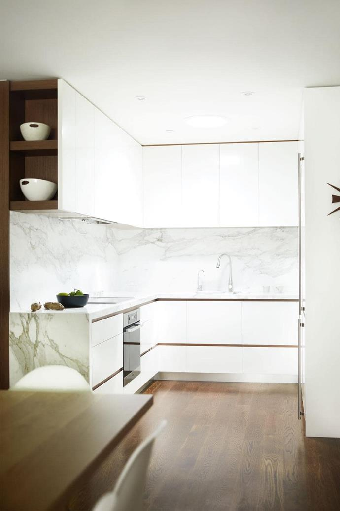 Marble offers dimension to the pared-back kitchen. Having walnut flooring throughout helps to connect the living and dining areas making the space look bigger.