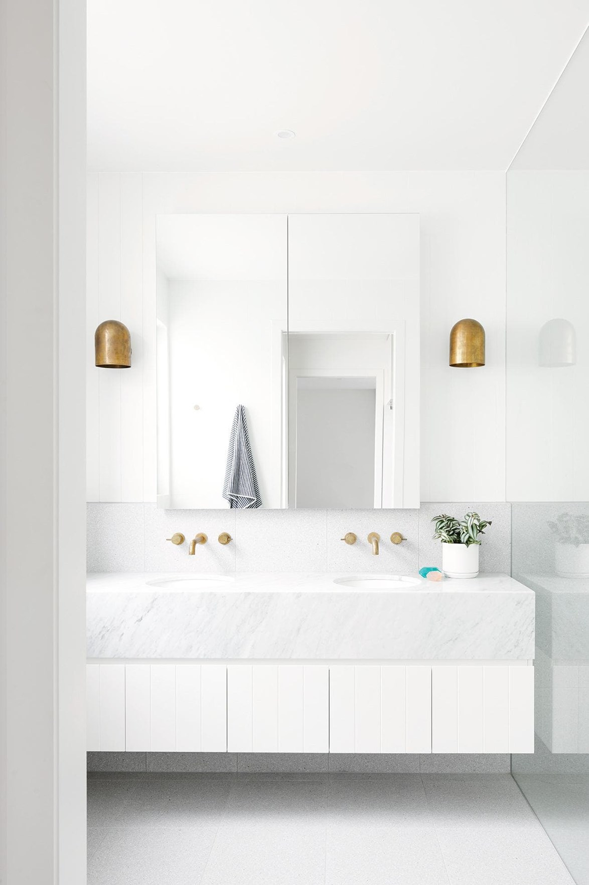 "When creating an all-white bathroom it is crucial to think about texture. This bathroom in a [contemporary Geelong home](https://www.homestolove.com.au/this-contemporary-geelong-home-was-built-in-just-five-months-17561|target=""_blank""), features a Carrara marble vanity and terrazzo flooring which stops the room feeling washed out. *Photo: Nikole Ramsay / Styling: Emma O'Meara*"