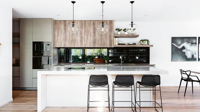 "This kitchen and dining zone in a [prefab house built in just six weeks](https://www.homestolove.com.au/prefab-perfection-from-empty-block-to-new-home-in-6-weeks-15589|target=""_blank"") enjoy views of the pool and backyard."