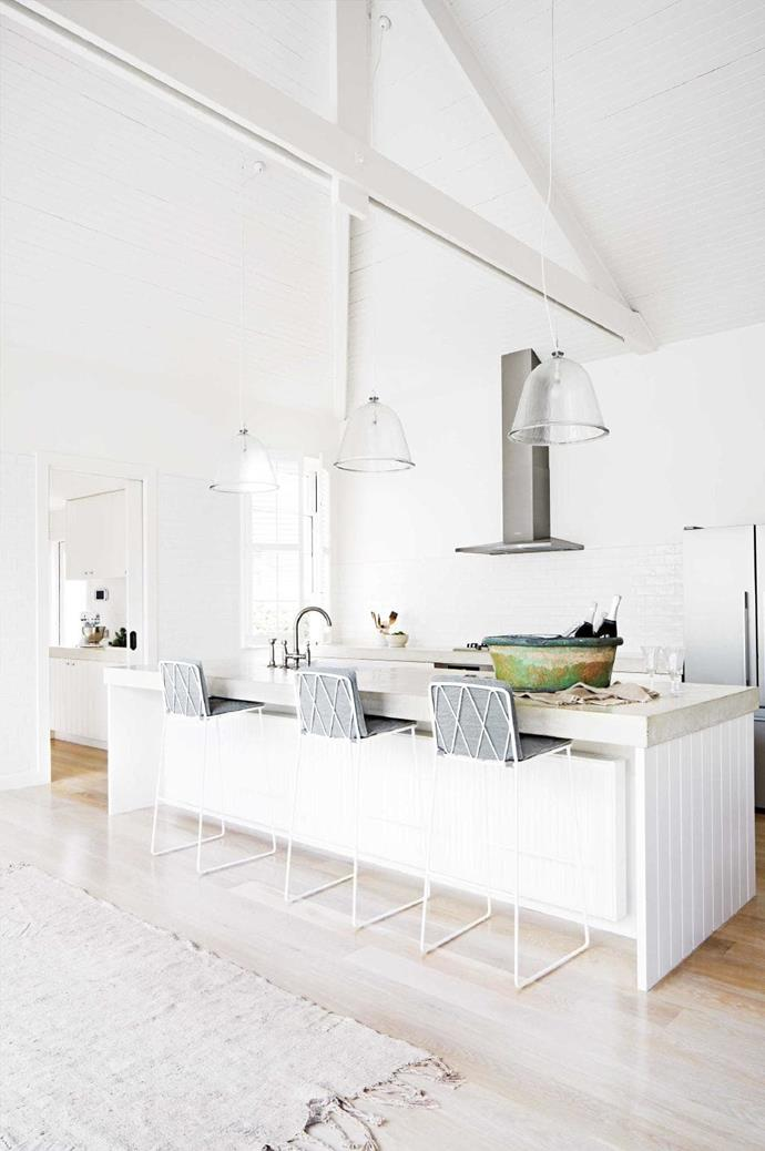An elegant all-white look is a style winner but to save this white-out from being too clinical, bring in a variety of materials in similar tones. In this open entertainer's kitchen, there are milky-white subway tiles on the splashback and tongue-and-groove panelling on the island bench to echo the slatted ceiling above. The plush grey stools offer a modern sophistication while the glass pendant lights take advantage of the high ceilings Stylist: Julia Green, Photographer: Armelle Habib