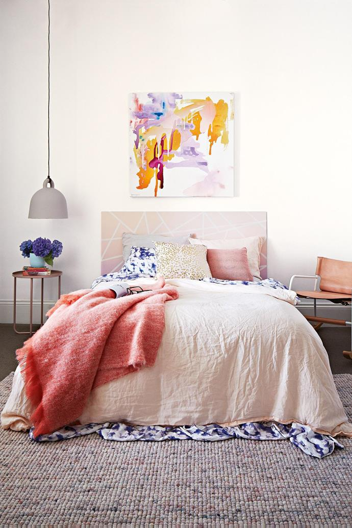 "**Heads up** A [custom bedhead](https://www.homestolove.com.au/bedhead-styles-we-want-to-wake-up-with-17215|target=""_blank"") sets the tone for the room, but it doesn't have to be complicated (or expensive). Here, plywood is painted with a graphic design to suit the blushing palette and complement the Prudence Caroline artwork. *Design: [Julia Green](https://greenhouseinteriors.com.au/