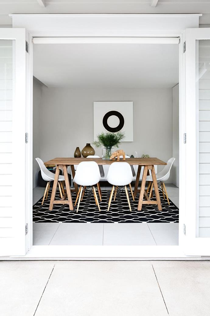A timber table and plush rug add instant warmth to a white-wash room Stylist: LeeAnn Yare, Photographer: Larnie Nicolson