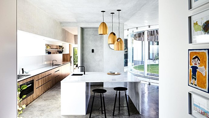 """**All wrapped up** This contemporary space features feathered concrete on the walls and ceiling, softening the look of the curved glass wall and polished concrete floor. The fridge and pantry are screened from the adjacent communal area to keep the look clean and simple, while a large Carrara marble slab forms the island benchtop. A trio of Ross Gardam timber pendant lights adds warmth opposite Polytec cabinetry in Sepia Oak Ravine. Design: [Steve Domoney Architecture](http://domoneyarchitecture.com/