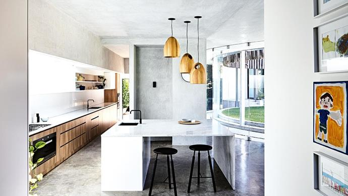 "**All wrapped up** This contemporary space features feathered concrete on the walls and ceiling, softening the look of the curved glass wall and polished concrete floor. The fridge and pantry are screened from the adjacent communal area to keep the look clean and simple, while a large Carrara marble slab forms the island benchtop. A trio of Ross Gardam timber pendant lights adds warmth opposite Polytec cabinetry in Sepia Oak Ravine. Design: [Steve Domoney Architecture](http://domoneyarchitecture.com/|target=""_blank""
