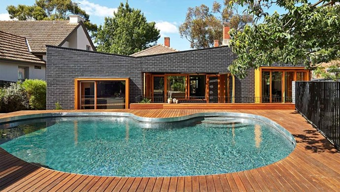"""Timber decking beautifully frames the stunning kidney shaped pool of this renovated Melbourne home. >> [See more of this home](https://www.homestolove.com.au/home-renovation-period-features-meet-modern-design-17490