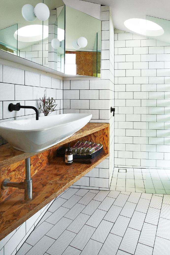 The combination of subway tiles, storage made out of OSB sheeting and exposed piping gives this bathroom a unique urban edge