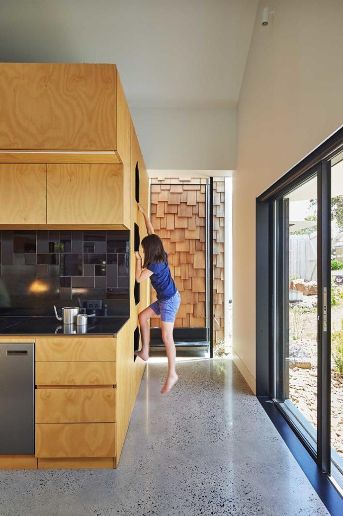 And even dad has his own getaway – climb the cutout ladder to the space above the kitchen cabinetry and find a small sanctuary clad in synthetic turf, a lone banana lounge the perfect spot to recline with a book.