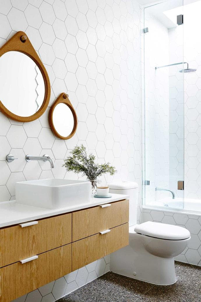 Choosing bathroom accessories in simple designs, from the cork mirrors, square basin to the timber drawers, allow the hexagonal tiles to be the stand out feature in the room