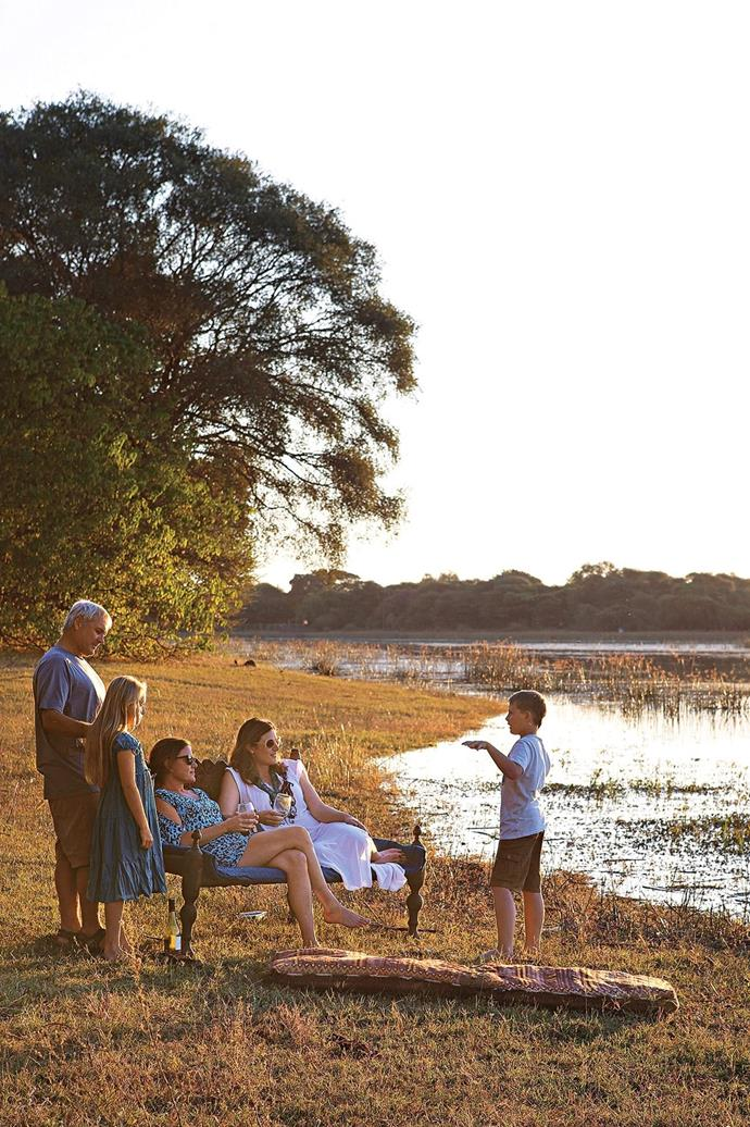 """**Exterior** With her partner Albert, his two children and her friend, textile designer Taryn Lamberti of Bead Studio, Darryl enjoys the evening sun by the Thamalakane River. [Read the full story here](https://www.homestolove.com.au/building-a-sustainable-rammed-earth-home-in-botswana-15548