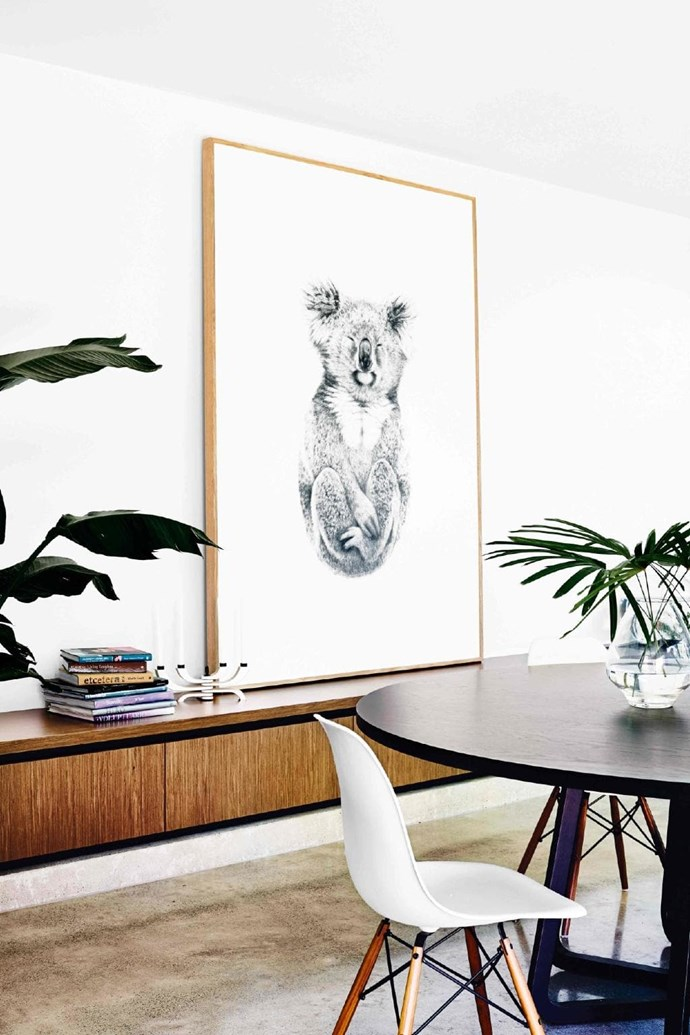 Displaying art can be a play of contrasting scale and shape. The sideboard in this dining area serves as a complementary platform for the expansive artwork by Carla Fletcher Stylist: Heather Nette King, Photographer: Derek Swalwell