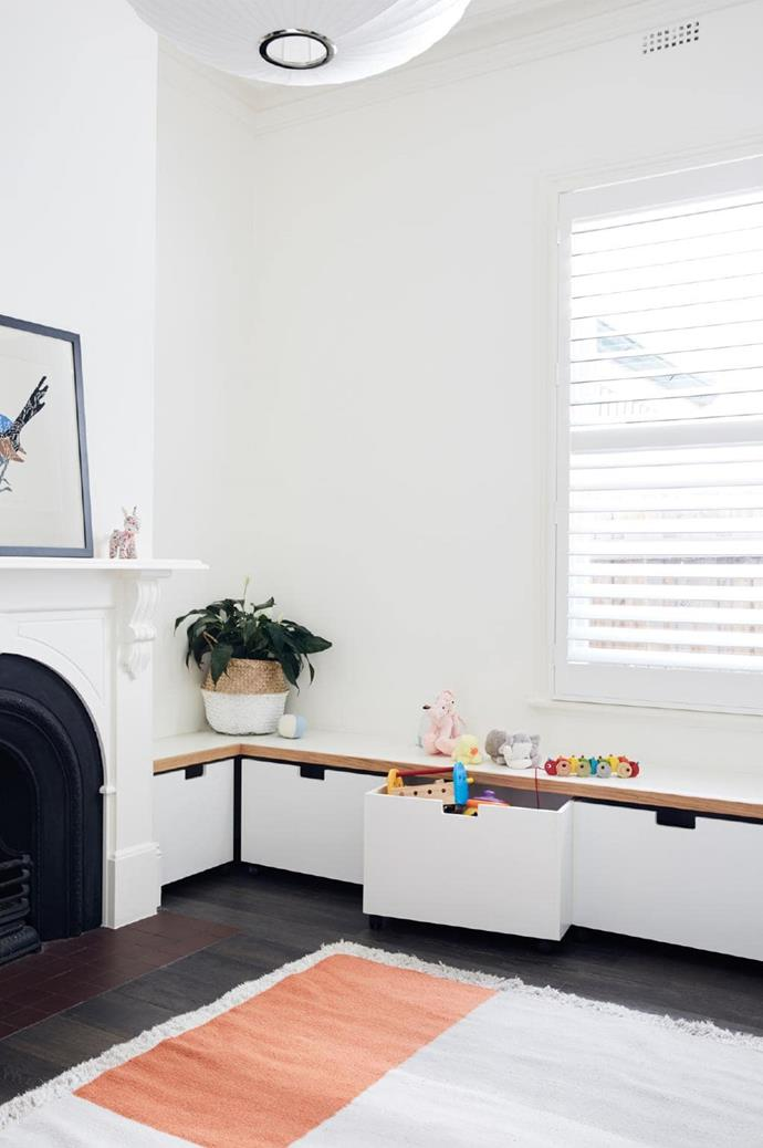 In the formal living room, bench seating doubles as clever toy storage.