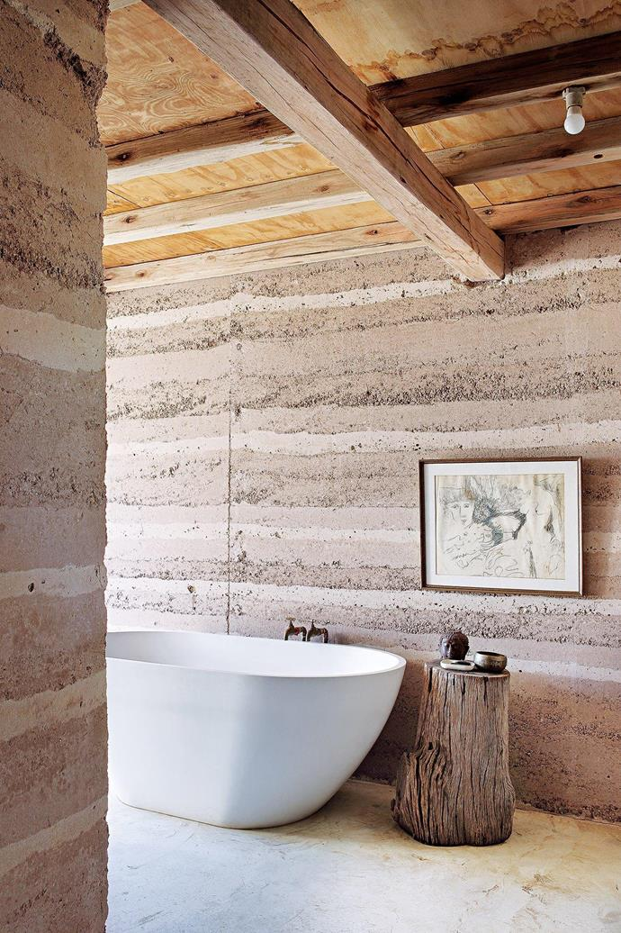 """**Ensuite** The shutterboards used to form the rammed-earth walls became the home's ceiling, but weren't limewashed in the bathroom. The freestanding tub and outdoor shower look out over the spectacular view. One of Darryl's friends used a trunk of leadwood to make the log stool. Artwork by BS Wahl. [Read the full story here](https://www.homestolove.com.au/building-a-sustainable-rammed-earth-home-in-botswana-15548