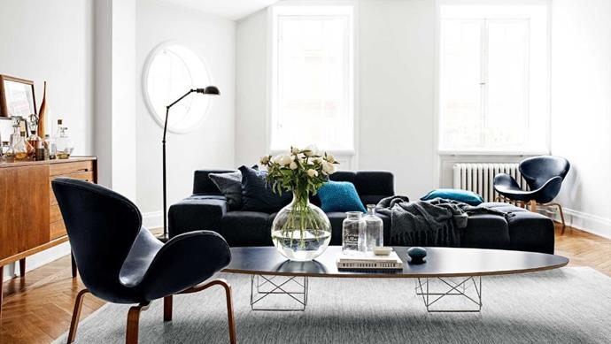 """A midnight-blue B&B Italia 'Tufty-Time' sofa by Patricia Urquiola is at the core of this inviting space. """"The table is an Eames,"""" says Evelina. """"We've been collecting mid-century modern furniture for some time. The 'Swan' chairs by Arne Jacobsen – we'll never get tired of them. The sideboard is from the '60s."""""""
