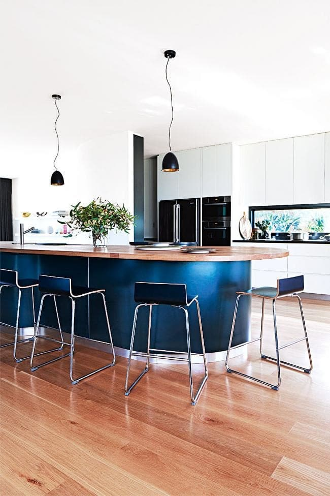 **Curve it up** European oak features on the island benchtop, as well as on the floor. The black facade and stainless-steel kickboards lend a touch of luxe. *Photographer: Armelle Habib*.