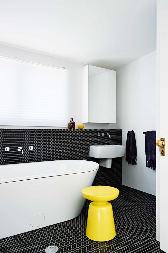 The size and depth of this large white tub is emphasized against the backdrop of black hexagon tiles Photographer: Anson Smart, Stylist: Maria Dyoniziak