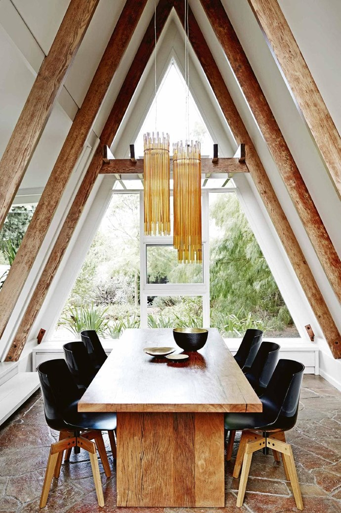 Set in the home's unique A-frame, this space features the original stone floor. Owner Jung made a model of the lights – Vistosi 'Diadema' pendant lamps imported from Italy – from paper and chopsticks to ensure they were hung at exactly the right height. A Mark Tuckey table is teamed with MDF Italia 'Flow' chairs from Hub Furniture Stylist: Tamara Maynes & Carly Spooner, Photographer: Mark Roper