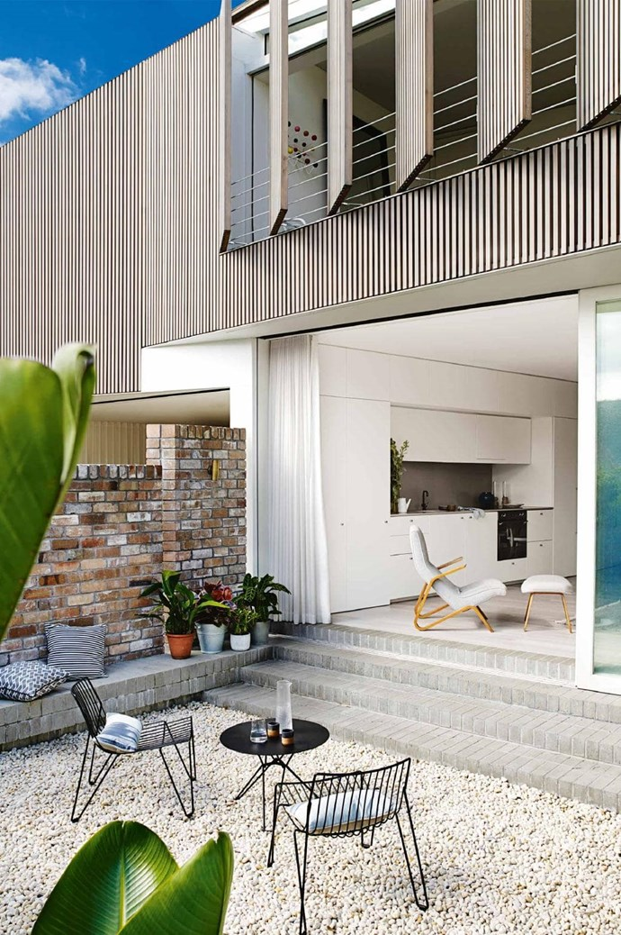 Pebbles and pot plants are great easy-to-maintain options for a courtyard. Sliding doors connect the indoor and outdoor areas making it feel like one big space. *Photo:* Prue Ruscoe   *Styling:* Claire Delmar