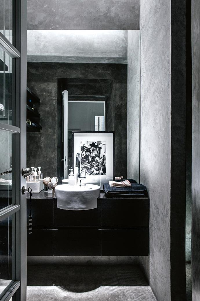 The cool, matt concrete finish gives the bathroom a luxurious feel. Moody black and grey tones create a quiet, calm feeling. Photographer: Stefania Giorgi