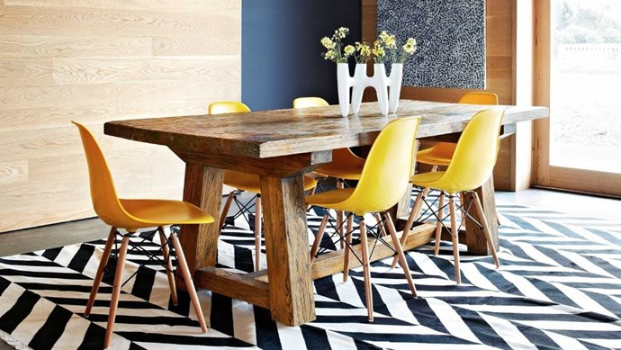 A black-and-white rug from Fenton & Fenton sets up a dramatic stage for the dining table, while yellow chairs add a sunny burst of colour Stylist: Julia Green, Photographer: Armelle Habib
