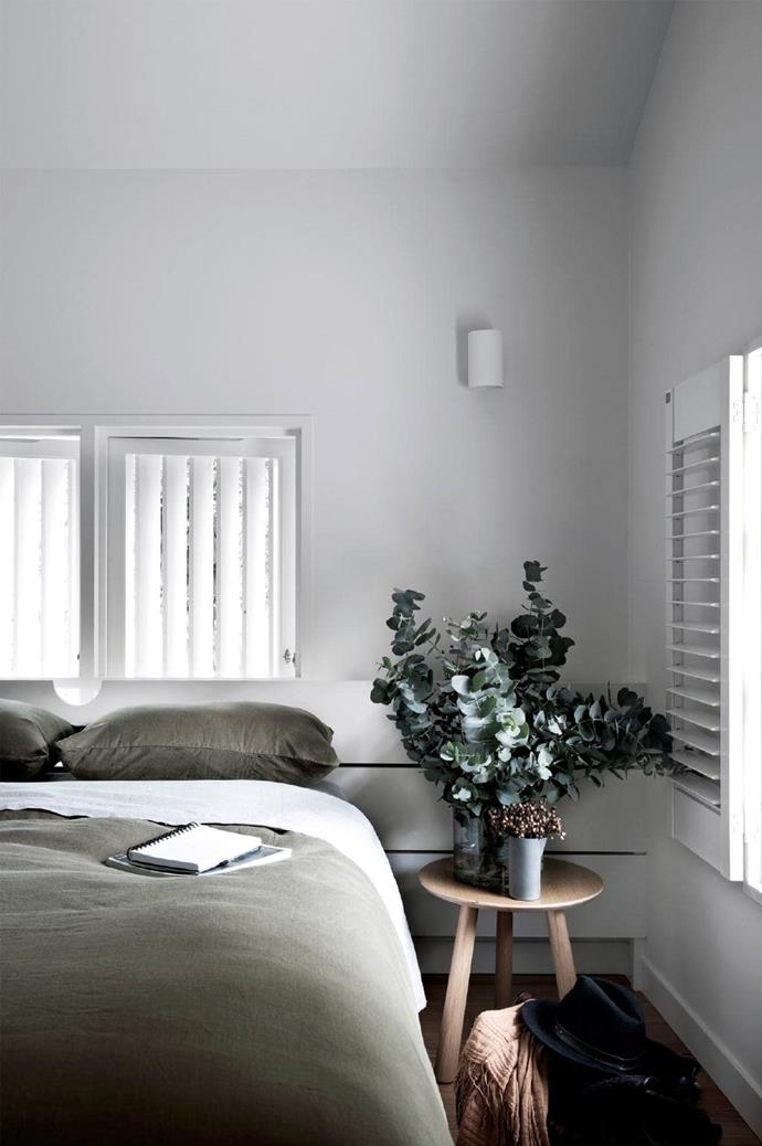The stark white seen throughout the home is lifted with hits of natural colours, such as the sage from the bedlinen and the warm timber grains of the bedside table. <br><br>**Tip**: Foliage is a great finishing touch – it's not always all about the flowers!