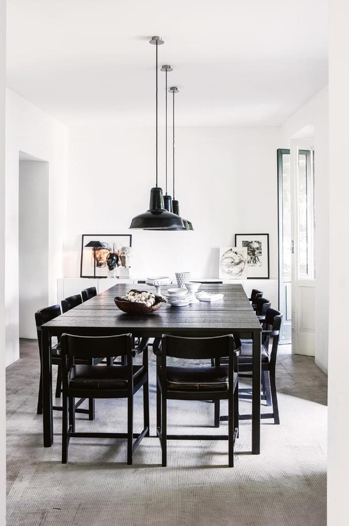 For keen entertainer Pietro, a large dining table is a must. Charcoal tones balance the neutral walls and floor, while the pendant lights offer a focus over the timber table. Photographer: Stefania Giorgi