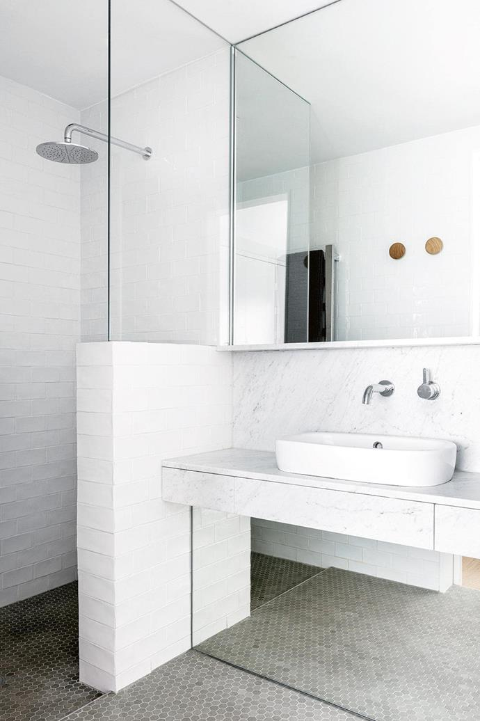 "Textural subway tiles in white create interest in this [monochrome bathroom](https://www.homestolove.com.au/small-bathroom-renovation-monochrome-magic-16123|target=""_blank""), while a mirrored kickboard beneath the vanity maximises the available light."