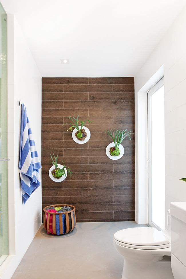 Make use of the steamy conditions in the bathroom for plants such as these elkhorns, which love humidity. An often overlooked spot for greenery, bathrooms are the best room for it. Save on water bills and take moveable pots into the shower with you to give your plants a good dose of H20. Photo credit: Dkor Interiors